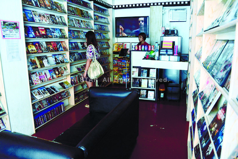 The theater houses over 1,000 original DVDs and Blu-Rays. Customers also have the option of browsing through the movie selection using the iPad by the counter. (Arni Aclao photo)