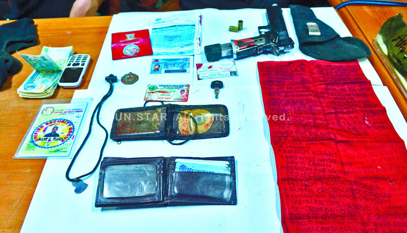 RECOVERED. Investigators display the items recovered from an alleged member of a kidnap-for-ransom group that was killed in a shootout with authorities last Monday. The sheet on the right, believed to be an amulet, contains cryptic phrases. (Amper Campaña of Sun.Star Cebu)