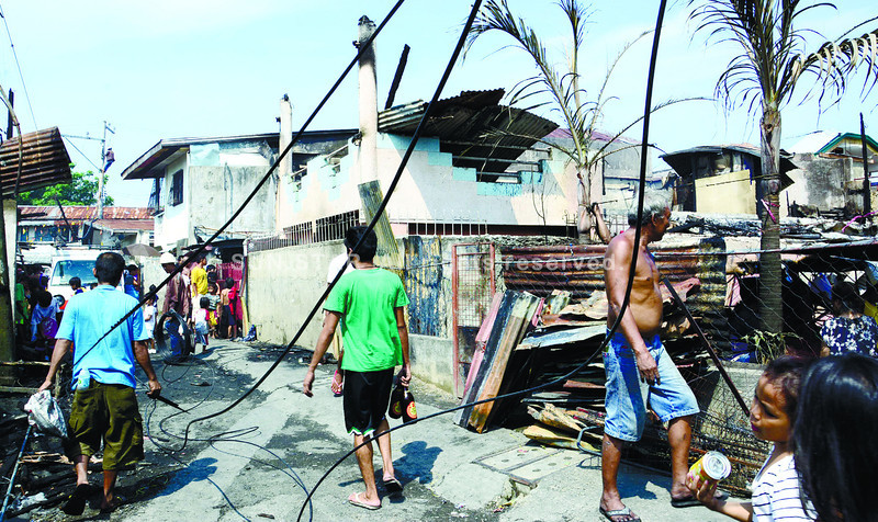 A man looked at the house where couple Margarita and Edgardo Miego's charred bodies were found after a fire hit an area in Barangay Labangon, Cebu City past 2 a.m. Wednesday. (Photo by Allan Cuizon of Sun.Star Cebu)