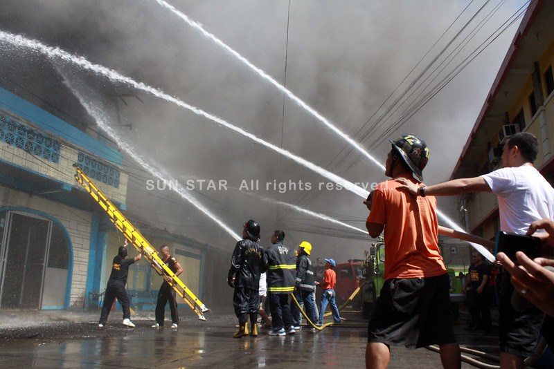 Firemen from different fire brigade in the city fought the fire that burned down a funeral parlor on Monday afternoon along Tiano Brother's Street in Cagayan de Oro City. cadavers were removed before they were damaged by the fire. no one is reported  (bobby lagsa)