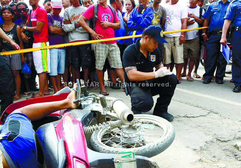 A member of the Soco team gathers evidence beside the fallen body and motorcycle of 33-year-old habal-habal driver Je Rod Baliras, who was reportedly shot dead by a man on a motorcycle in Barangay Cansaga, Consolacion, Cebu at 5:15 a.m. Saturday, June 22, 2013. (Allan Cuizon photo/Sun.Star Cebu)