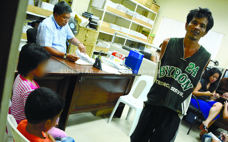 SON'S KILLER?  Reynaldo Labitad (in jersey) is presented to Talisay City Prosecutor Marshall Rubia (seated behind the desk) for the filing of charges of frustrated murder and child abuse. Labitad's two children (left foreground) say they saw their father kill their 13-year-old brother. (Alex Badayos photo)