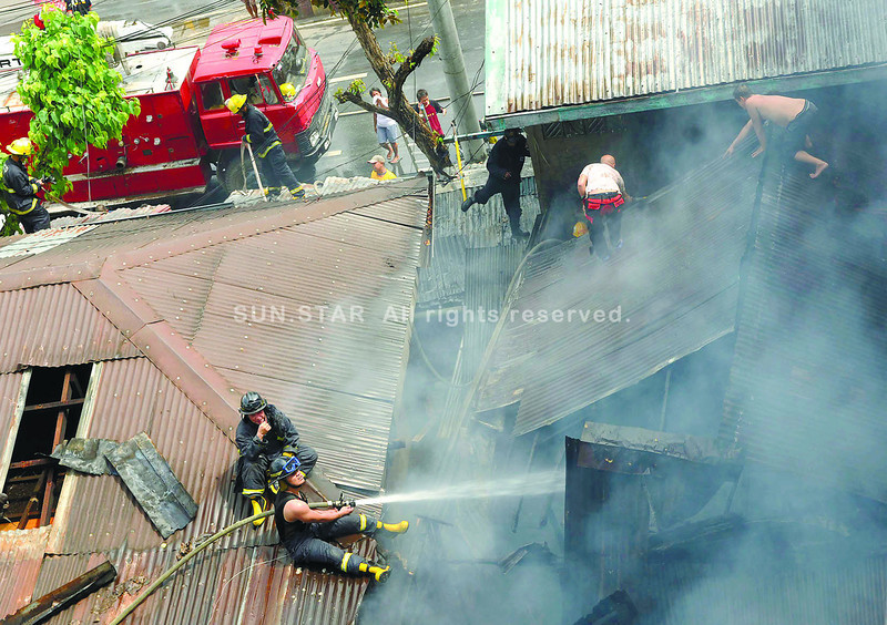 Kept by narrow roads from reaching a fire scene, firefighters clamber atop the neighborhood's roofs to reach the distressed area. The fire hit Duljo-Fatima in Cebu City around 9:10 a.m. Saturday, June 22, 2013. (Arni Aclao photo/Sun.Star Cebu)
