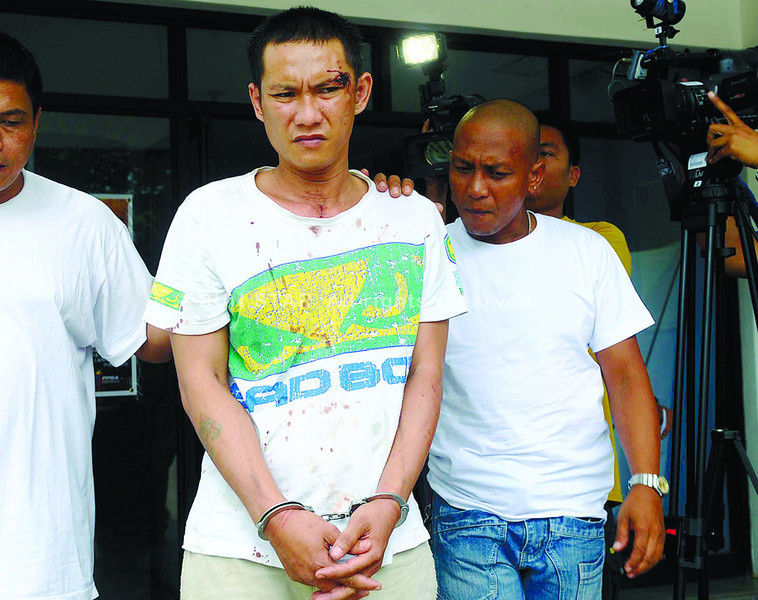 CEBU.  Ian Canseco (top, in handcuffs) is arrested on suspicion of being one of the two men who beat and shot to death a police officer who was chasing the men who stole his motorcyle helmet. (Arni Aclao)