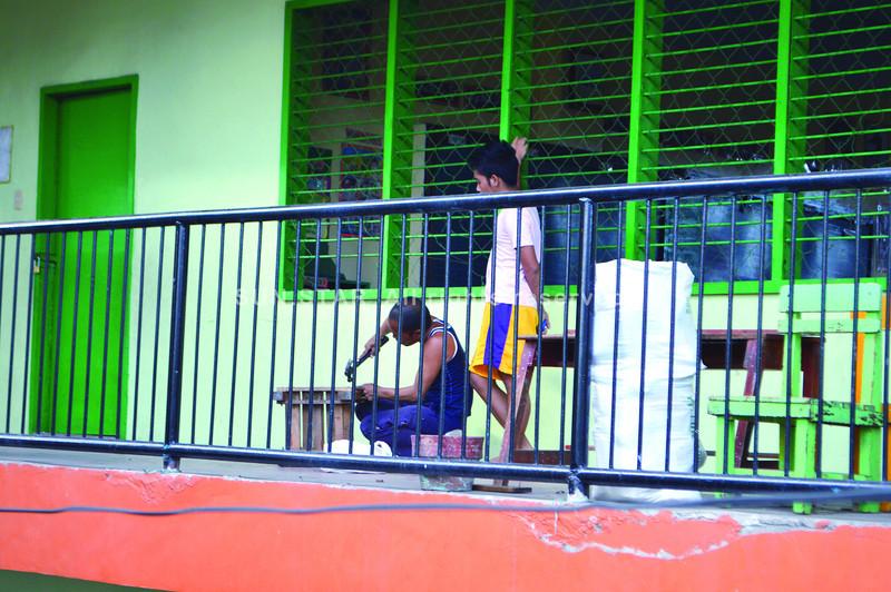 NECESSARY DESKWORK. A carpenter fixes some desks in the Regino Mercado night high school on Panganiban St. in Cebu City.   (Sun.Star Foto/Alan Tangcawan)