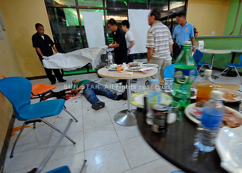BRAZEN. Tables are still full of leftover food from a gathering of marketers of Vital-C as funeral workers prepare to take out the body of business owner Richard L. King after he was shot dead in front of his distributors inside the Vital-C office along Sobrecarey Street in Barrio Obrero. (King Rodriguez)