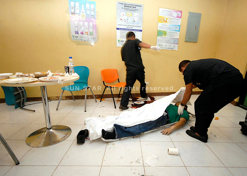 DEAD BODY. Authorities cover the dead body of Cebu-based businessman Richard King who was shot to death by an unidentified gunman. King was in Davao City for a gathering of marketers of Vital-C, one of his businesses. (King Rodriguez photo)