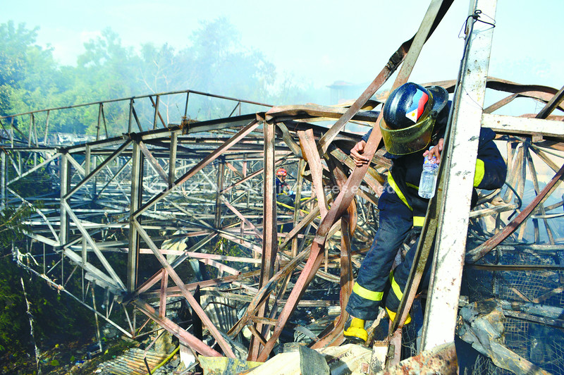 TANGLED. Firefighters check under a fallen billboard in Barangay Banilad, Cebu City to make sure a fire that ruined 24 houses no longer had any burning embers. (Sun.Star photo/Alan Tangcawan)