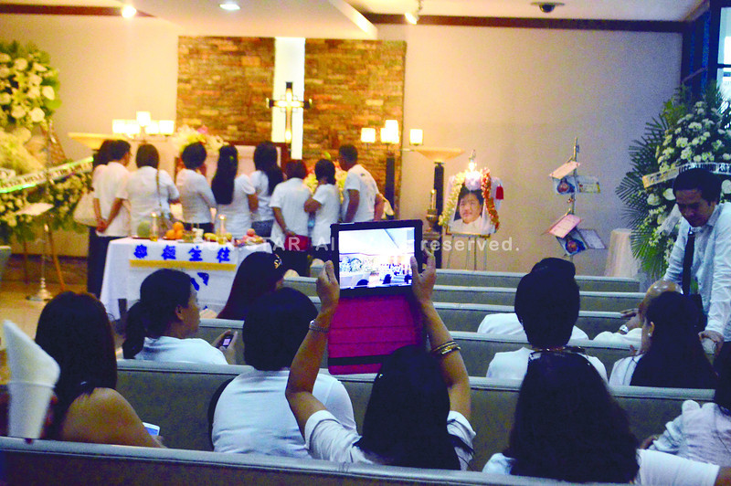 KING'S WAKE. Employees of Richard King pay their last respects at his wake at the St. Peter's Funeral Homes on New Imus Road in Cebu City. King's remains arrived from Davao City yesterday morning. (Sun.Star photo/Alan Tangcawan)
