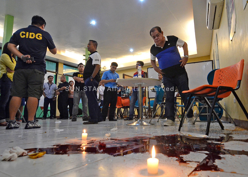 DAVAO. Davao City Police Office chief Vicente Danao (center) check out the scene of the crime along with several police officers and staff of Vital-C. (King Rodriguez)