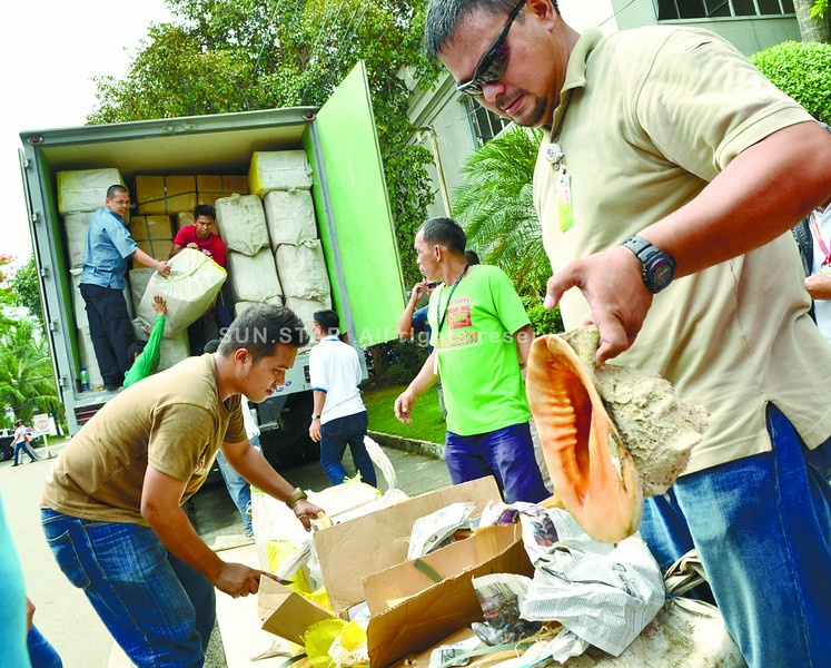 CEBU. Loy Anthony Madrigal (right), head of the Cebu Provincial Anti-Illegal Fishing Task Force, shows some of the shells his team intercepted. These were loaded in a cargo truck that, according to the driver, contained dried fish from Zamboanga del Norte. (Sun.Star photo/Amper Campaña)