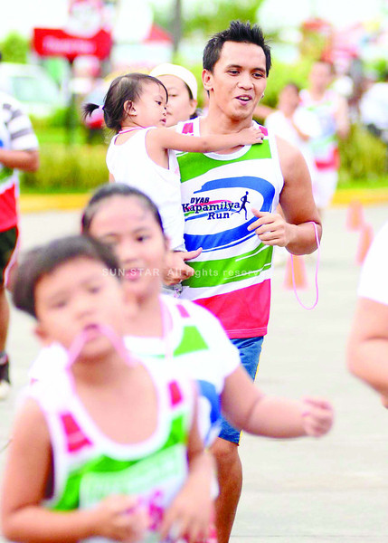 FATHER'S DAY RUN. A runner carries his daughter during the Kapamilya Run at Parkmall in Mandaue City. (Sun.Star Photo/Ruel Rosello)