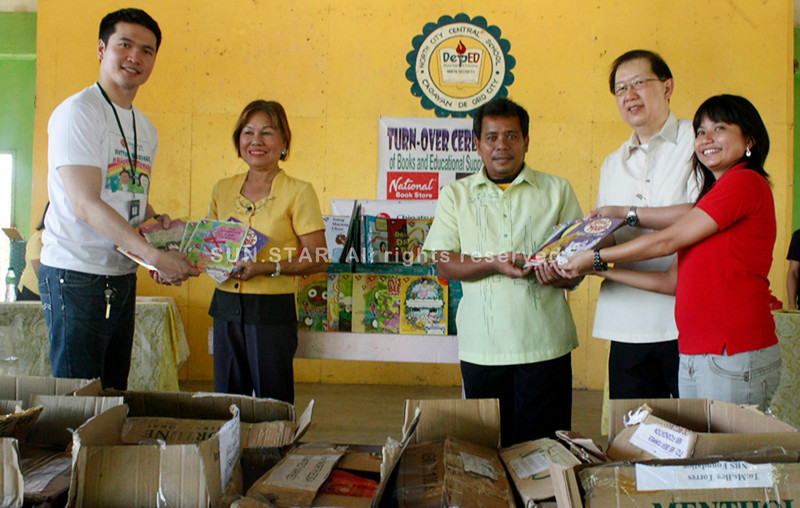 CAGAYAN DE ORO. Chinatrust (Phils) Commercial Bank and National Book Store Foundation Inc.(NBSFI), turn over hundreds of books to elementary pupils at Puntod elementary school on Tuesday. Victor Lim (second from right), group head of Chinatrust lead the activity along Ari Rivera (extreme left), Chinatrust, Branch Manager; and Bea Andrea Torres (extreme right), NBSFI, Program Manager, hand over the books to Dr. Lydia Getueza (second from left), North City Central Supervisor; and Romeo Beslig, Puntod Elementary School Assistant Prinsicpal during a simple ceremony. (Joey P. Nacalaban)