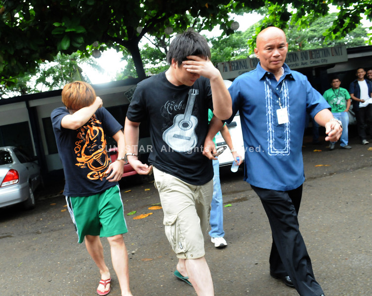 CEBU. The two Korean nationals who were accused of raping two Japanese women head for the Criminal Investigation and Detection Group office in Cebu City, escorted by Insp. Delfin Bontuyan (right). (Allan Defensor)