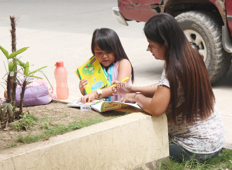 CAGAYAN DE ORO. A mother helps her child fill up her notebook during Monday's first day of school. (Joey P. Nacalaban)