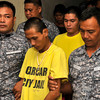 A CHARGED EXPERIENCE.  Carcar City jail guards escort Jaybhoy Lauron (front, in yellow T-shirt) and Jethro Lapiña (behind Lauron) to the Regional Trial Court for their arraignment.  (Alex Badayos)