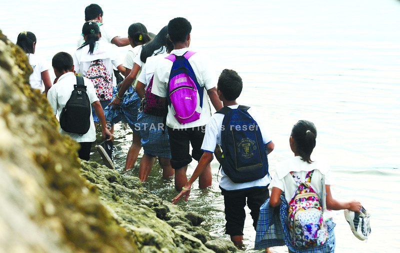 CEBU.  For some children in Bantayan town, the walk to and from school involves wading in low tide to another island. A paddleboat is required at high tide. (Alex Badayos)
