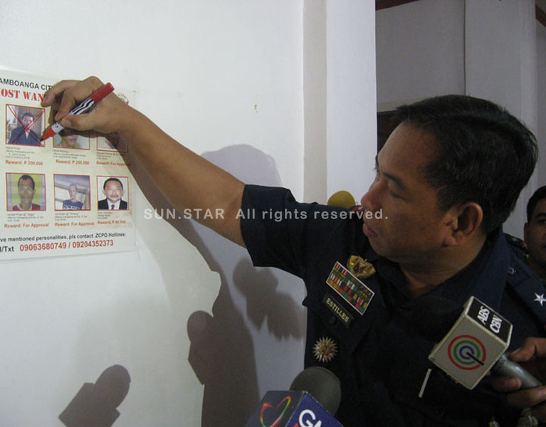 ZAMBOANGA. Police Regional Office Director Napoleon Estilles marks cross the photograph of kidnap gang leader Wahid Pingli, who was killed in a clash Sunday in Sacol Island, Zamboanga City. (Bong Garcia)