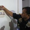 ZAMBOANGA. Police Regional Office Director Napoleon Estilles marks cross the photograph of kidnap gang leader Wahid Pingli, who was killed in a clash Sunday in Sacol Island, Zamboanga City. (Bong Garcia)