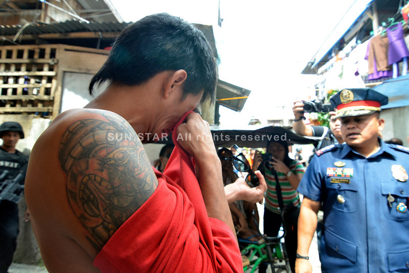 DAVAO. Boloy Sino wipes his eye after being awakened to face City Police director Ronald Dela Rosa during the Oplan Tokhang, a visitation on houses of suspected drug pusher by the police. (King Rodriguez)