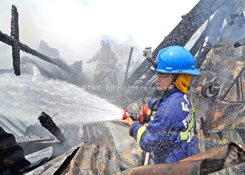 DAVAO. Firemen combat with yet another fire, this time in Purok 24 Sargasay, Barangay Maa, on Wednesday. Seven houses were razed. (King Rodriguez)