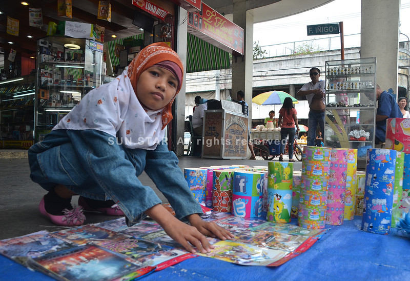 DAVAO. A young girl holds down DVDs as a strong gust of wind threatened to blow these away. It's back to normal business for sidewalk vendors along San Pedro Street as Araw ng Dabaw is now over. (Seth delos Reyes)