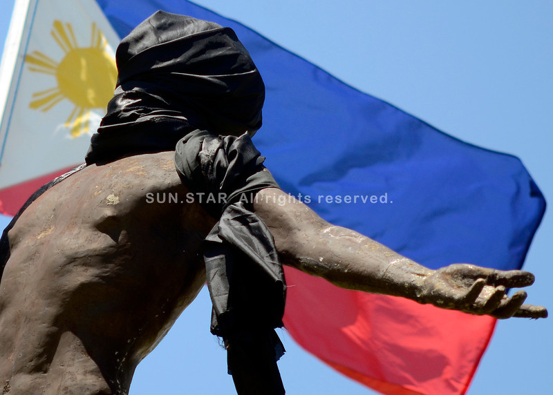 DAVAO. The Oblation of the Philippines, symbolizing selfless offering of one's self for one's country, is smothered with black cloth as a sign of protest by students on the death of UP Manila student, Kristel Tejada. (King Rodriguez)