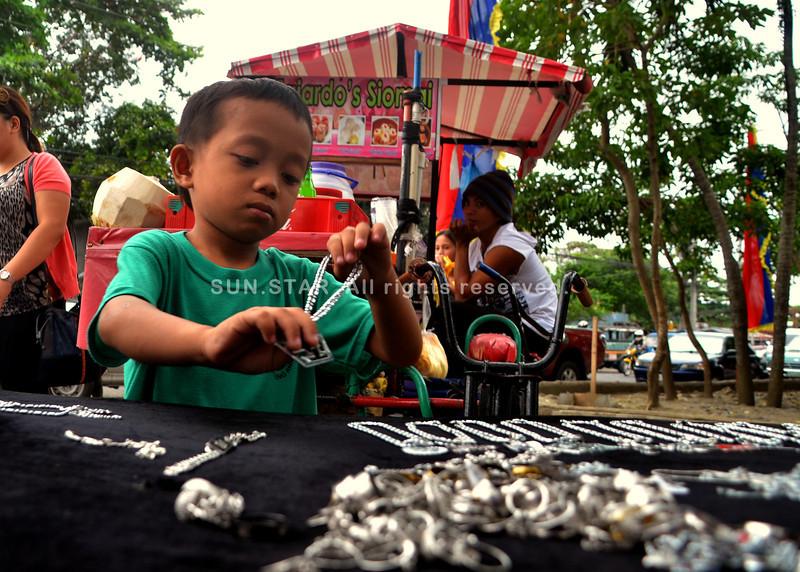 DAVAO. Bataang lalaki mitabang sa iyang amahan pag-display sa ilang baligya nga kwentas sa Osmena Park, dakbayan sa Davao kagahapon. (Seth delos Reyes)
