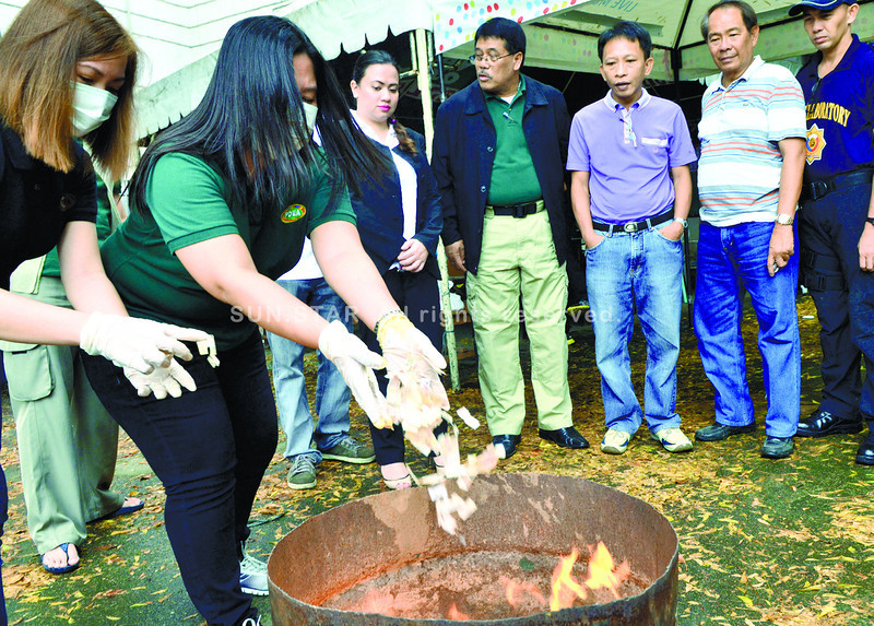 RTC Branch 8 court Judge Macaundas Hajirazul (3rd from right) together with PDEA 7 officer in Charge Esperidion Javier (center, in black jacket) and other officials burned the illegal drugs this morning at the Palace of Justice........(Sunstar-Amper Campaña   3 13 2014)