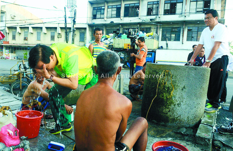 CEBU. City Mayor Michael Rama washes his face at a community well along Sergio Osmeña Ave. during a walkthrough early Tuesday morning. (Arni Aclao)