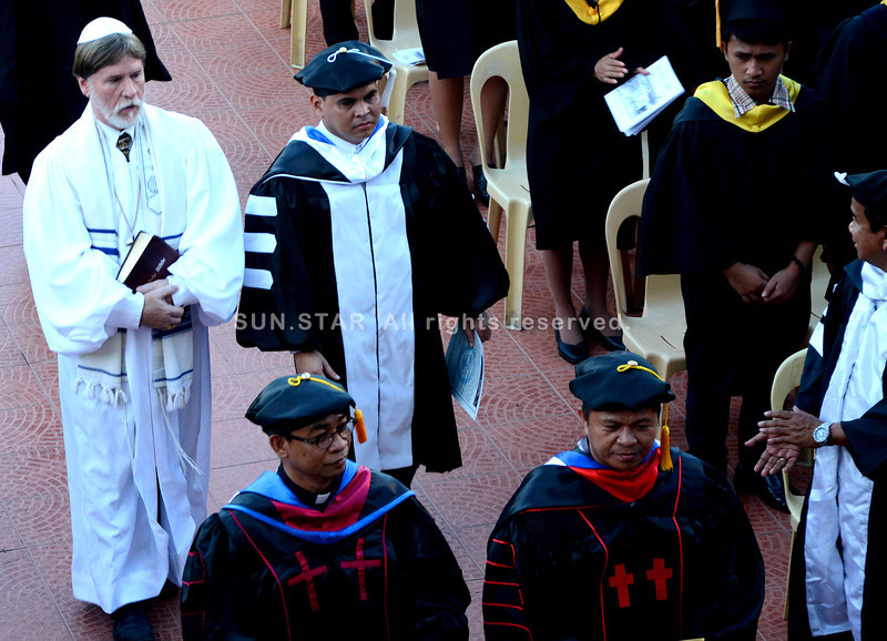 GRADUATION REPEATED. Unmindful of the protest seeking his ouster as Talisay City College president, Dr. Paulus Cañete (above photo, in black and white toga), together with Northwestern Christian University president Bishop Dr. Howard Sarkela (in white cassock) and other TCC faculty members, proceeds with the second graduation ceremony at the Talisay City Hall. (Alex Badayos)