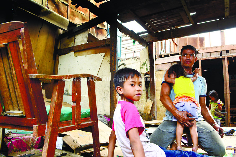BORROWED TIME. Florito Abulencia comforts his twoyear-<br /> old daughter Loraine Ace in what's left of their demolished<br /> house on J. de Veyra St. in this photo taken<br /> last March 11. The court has ordered the demolition of<br /> at least 117 houses in Barangay Carreta, Cebu City, after<br /> upholding a private person's claim over the property.<br /> (SUN.STAR FOTO/ALLAN CUIZON)