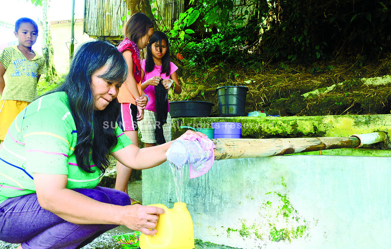 CEBU. A resident of Barangay Montealegre in Tuburan uses a handkerchief as a filter for her family's water supply from a spring. (Allan Cuizon)