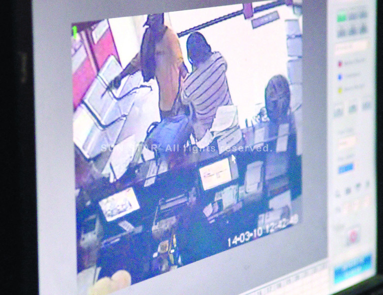 A robber, in yellow T-shirt and armed with a gun, is shown in the CCTV footage during the heist on a LBC Taboan branch. (Photo by Amper Campaña of Sun.Star Cebu)
