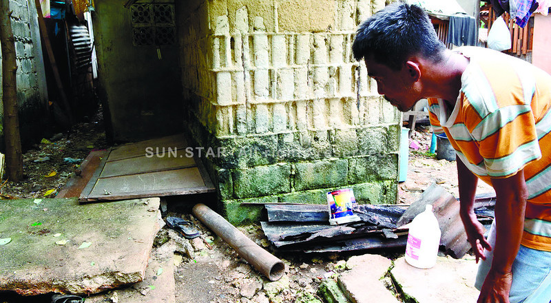 A resident takes a look at an opening of a septic tank where three people died, including a 16-year-old boy. (Sun.Star Cebu photo)