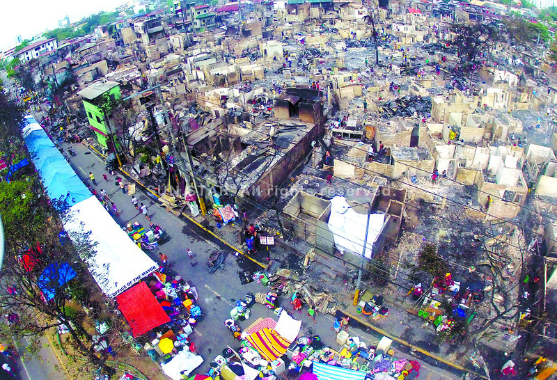 AFTER THE FIRE, STREET LIFE. Survivors take shelter under tents arranged in one lane of Imus Road in Barangay Lorega, Cebu City, while others search the ruins of some 500 houses to see if there was anything they could save after Tuesday's fi re. A camera mounted on a quadcopter shows how far into the community the flames spread. (SUN.STAR FOTO/KIM YUHICO)