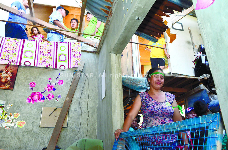 The demolition of one house in Apas, Cebu City drives a woman (right) to tears, while Apas Barangay Captain Ramil Ayuman (above, partly hidden by roof) pleads with court sheriff Edilberto Suarin and a demolition team to stop tearing down the rest of the 157 houses. (Amper Campana)