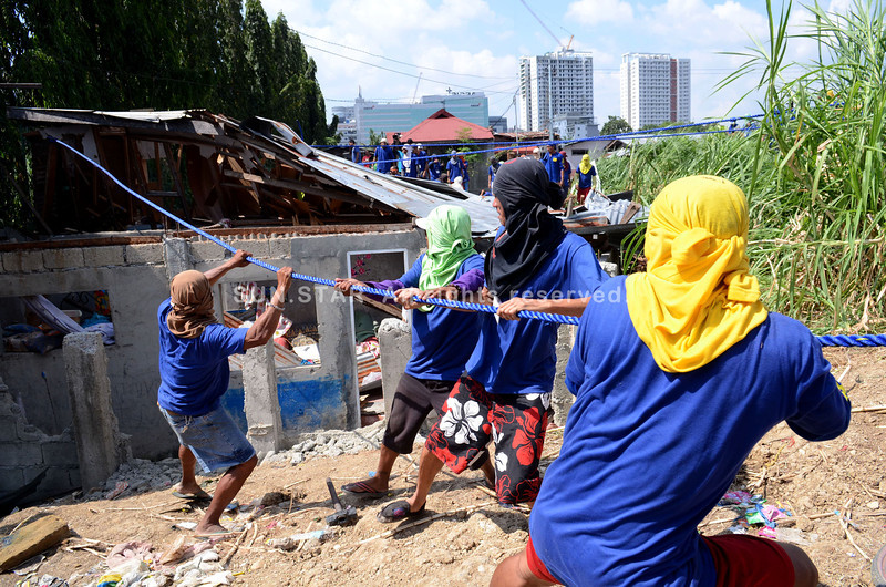 FIVE HOUSES DOWN SO FAR. A demolition crew tugs at the house of Joeman Bandillo, 1 of 5 houses torn down since last Tuesday. The crew is enforcing an order to demolish 157 houses in Barangay Apas, Cebu City. (Ruel Rosello)