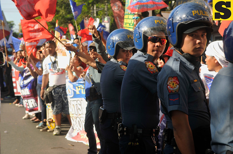 Riot policemen barricade a group of supporters