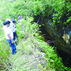 ANOTHER HOLE. Village officials check a hole in an upland barangay in Argao. Although the hole was observed last year, residents said it had grown bigger. (Jinky Bargio)