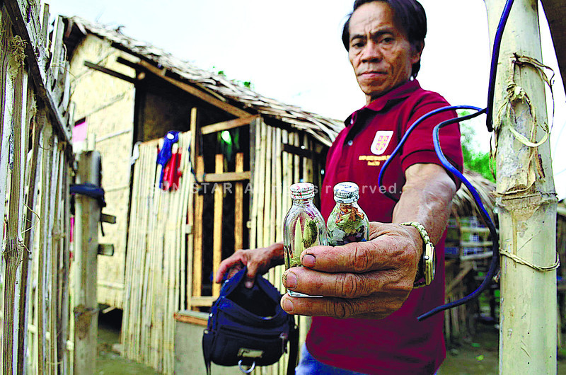 FOLK REMEDIES. Felipe Albero shows some of the concoctions that Marjilly Sanger, his son's live-in partner, used to sell. Both Marjilly and Albero's son Junie were shot dead in their home in South Poblacion, Naga City, Sunda. (Amper Campaña)