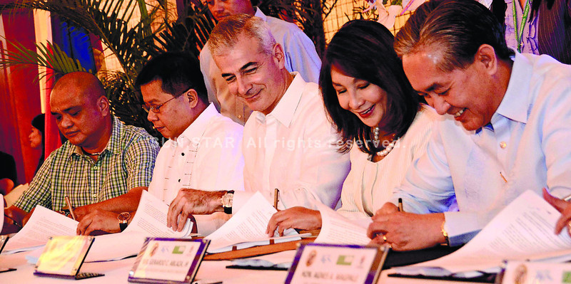 WATER DEAL. Cebu Gov. Gwendolyn Garcia (second from right) together with Manila Water Company chairman Fernando Zobel de Ayala (third from right), Manila Water Consortium chairman and president Gerardo Ablaza Jr. (right), PB Member Peter John Calderon (second from left) and Carmen Municipal Mayor Gerard Villamor (left) sign the Cebu bulk water joint project at the Capitol Social Hall. (Amper CampaÑa)