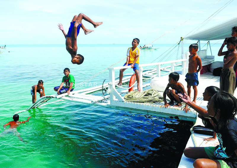 FLIPPING OUT AT SEA. Children of Caubian Island in Lapu-Lapu City have fun aboard a motor boat while its passengers take a tour of the island. (Arni Aclao)