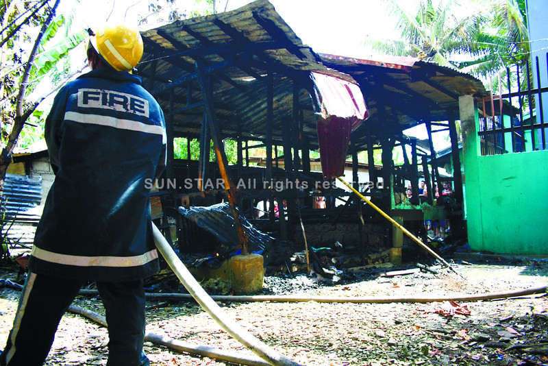 GREATER DISASTER AVERTED.  A firefighter checks for any remaining embers at the scene of a fire in Barangay Bankal, Lapu-Lapu City, where three children under the age of four were saved by their seven-year-old brother. (Alan Tangcawan)