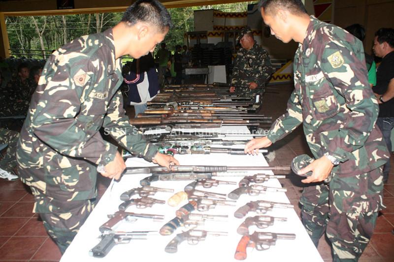 CAGAYAN DE ORO. Soldiers inspect the different firearms that were turned over by the rebels during the handover ceremony held in Malaybalay City on Thursday. (Joey P. Nacalaban)