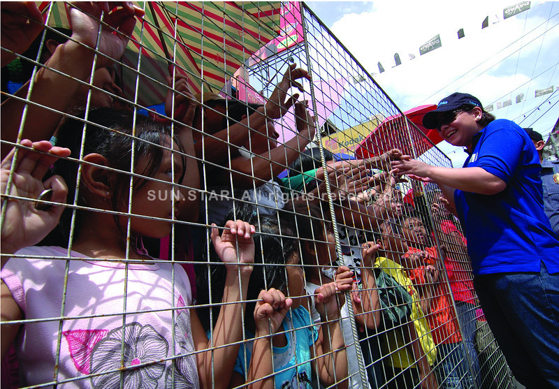 DAVAO. Young children stare motionless while the crowd behind them surge to shake hands with Davao City Mayor Sara Z. Duterte during the Parada Dabawenyo Friday. (King Rodriguez)