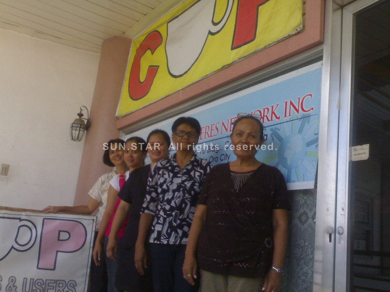 """CAGAYAN DE ORO. Staff members of the Consumers and Users Productive (CUP) association pose with CUP president Arlene Maagad (center) at its office in Bulua, Cagayan de Oro City. Nibocar """"Bon"""" Teves, the association's prime mover, consider them as the backbone force of CUP in Northern Mindanao. (Loui S. Maliza)"""