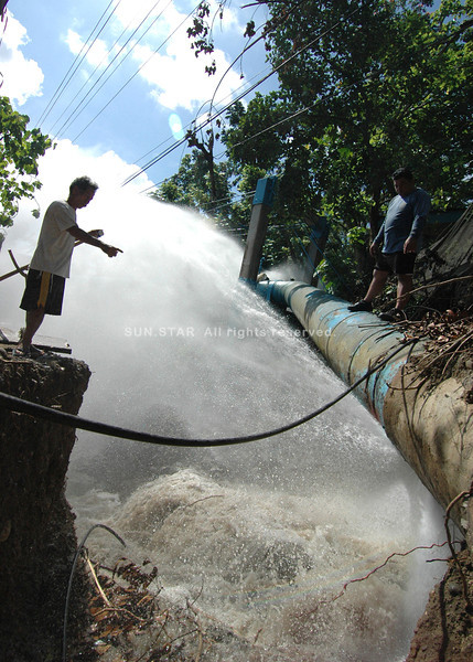 DAVAO. A man checks the jet of water streaming out of the main pipe of Davao City Water District as workers transfer the flow to their new waterway along the bridge at the Diversion Road in Maa. (King Rodriguez)