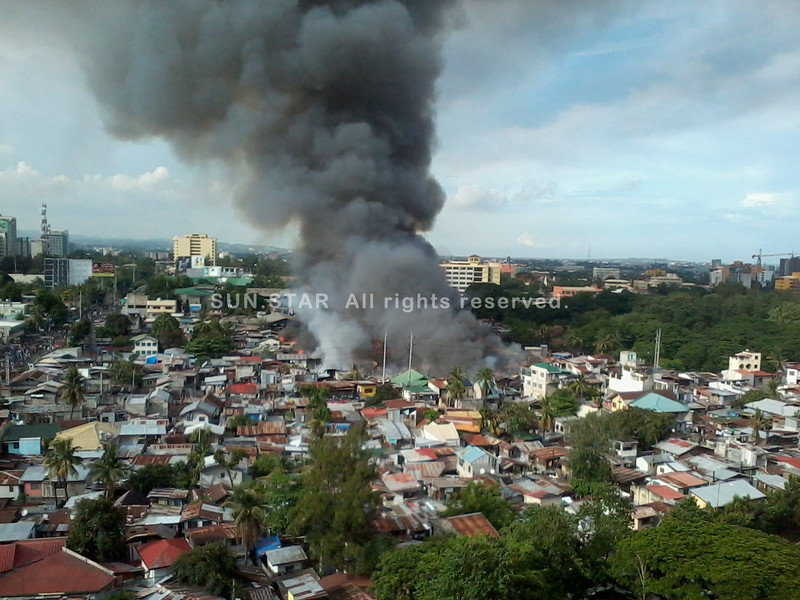CEBU. Thick, black smoke filled the sky above houses made of light materials that caught fire Friday in sitio Cabantan, Barangay Luz, Cebu City. (Photo by Gerome Dalipe of Sun.Star Cebu)