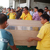 DAVAO. A wooden crate containing the remains of Apple Dayot Gamale, 23, a Dabawenya OFW, is being carried onto a van after its arrival at the Davao International Airport on Wednesday. (Arianne Casas)
